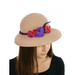 A felt hat with a large beige brim, decorated with felted flowers.