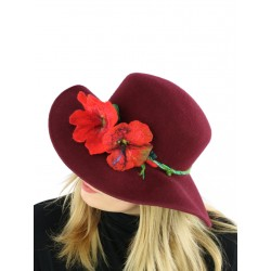 A maroon felt hat with a wide brim, decorated with a sprig of flowers