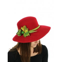 A red wide-brimmed felt hat, decorated with a twig with leaves.