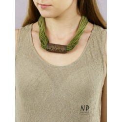 A green string necklace with a ceramic tube-shaped ornament.