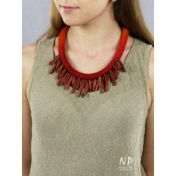 In a shade of red and orange, a handmade necklace made of cotton string and ceramic ornaments