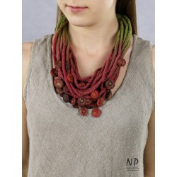 In shades of green, claret and dirty pink, a handmade necklace made of cotton string and ceramic ornaments