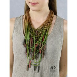 In the colors of green and honey, a handmade necklace made of cotton strings and ceramic ornaments