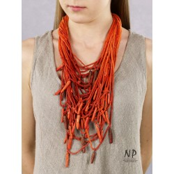 In the colors of red and orange, a handmade necklace made of cotton strings and ceramic ornaments