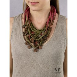 In the colors of green and dark pink, a handmade necklace made of cotton strings and ceramic beads