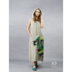 A linen dress with a hood, decorated with a hand-painted face in contrasting colors