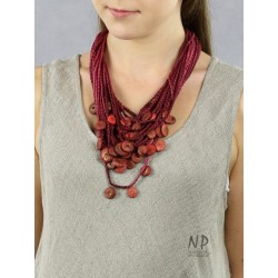In the colors of burgundy and dirty pink, a handmade necklace made of linen and cotton strings decorated with ceramics