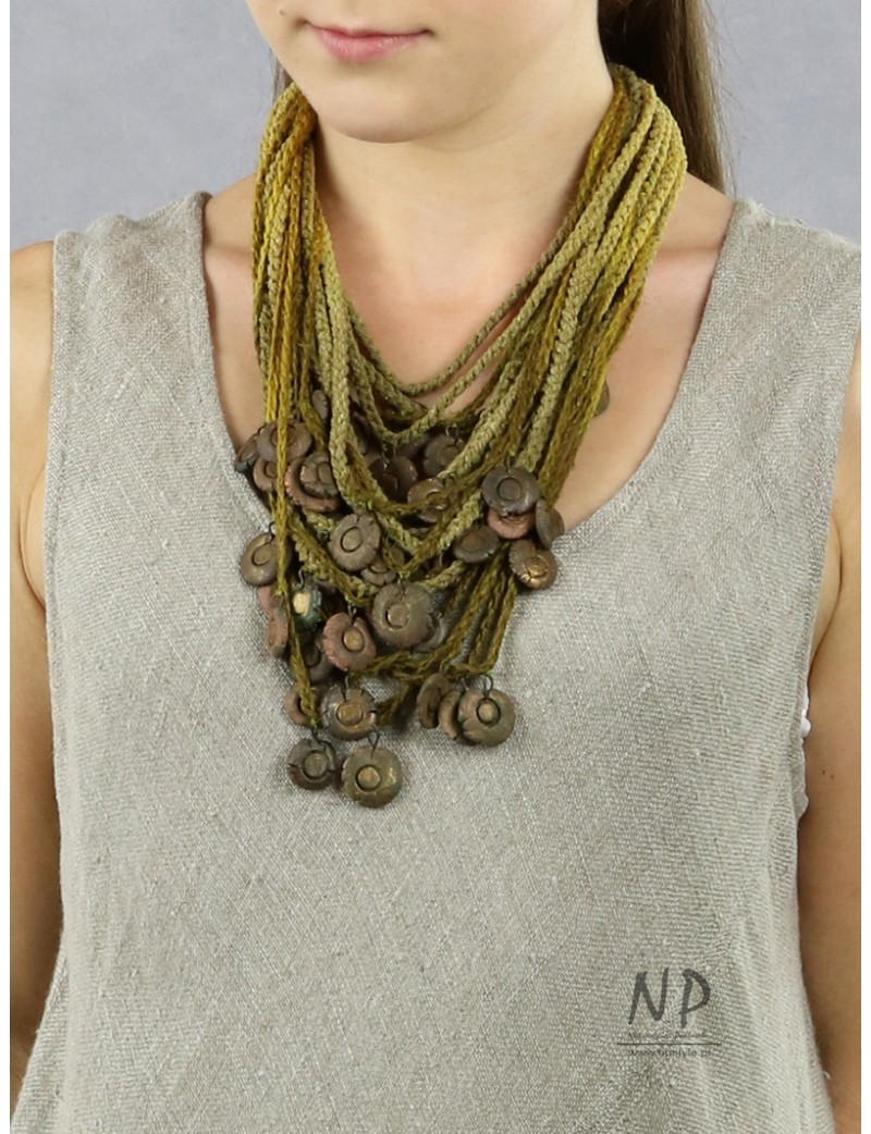 In green colors, a handmade necklace made of linen and cotton strings decorated with ceramics