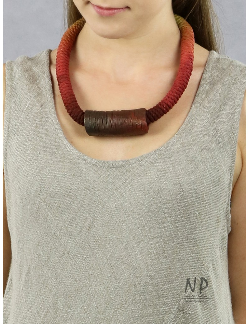 A handmade string necklace with a ceramic tube