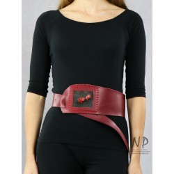 A wide decorative burgundy leather belt for the dress