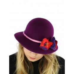 A felt hat with a large purple brim, decorated with felted flowers.