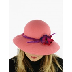 A felt hat with a large brim in pink color, decorated with felted flowers.