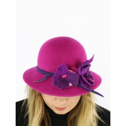 A felt hat with a large amaranth brim, decorated with felted flowers.